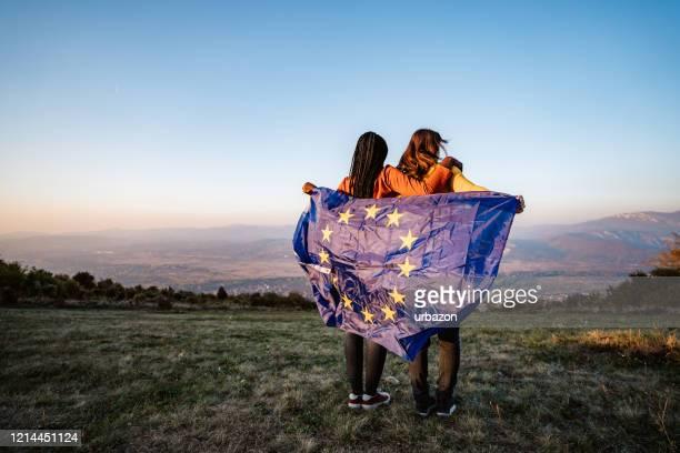 two multi-ethnic women holding european union flag - european union stock pictures, royalty-free photos & images
