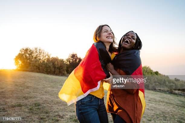 ドイツ国旗を掲げる2人の多民族女性 - 再統一 ストックフォトと画像