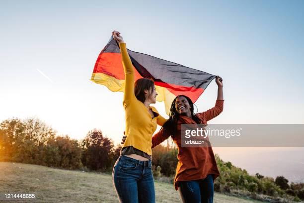 ドイツ国旗を掲げた2人の多民族女性 - 再統一 ストックフォトと画像