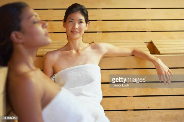 two multi-ethnic women relaxing in sauna - black woman in sauna stock pictures, royalty-free photos & images