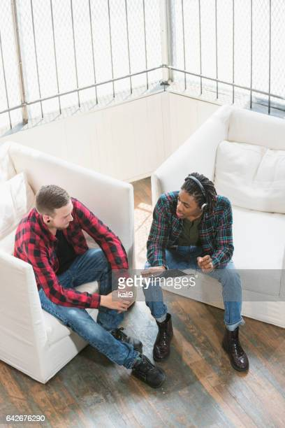 Two multi-ethnic young men discussing tablet computer