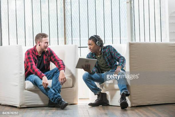 Two multi-ethnic young men sitting on chairs talking