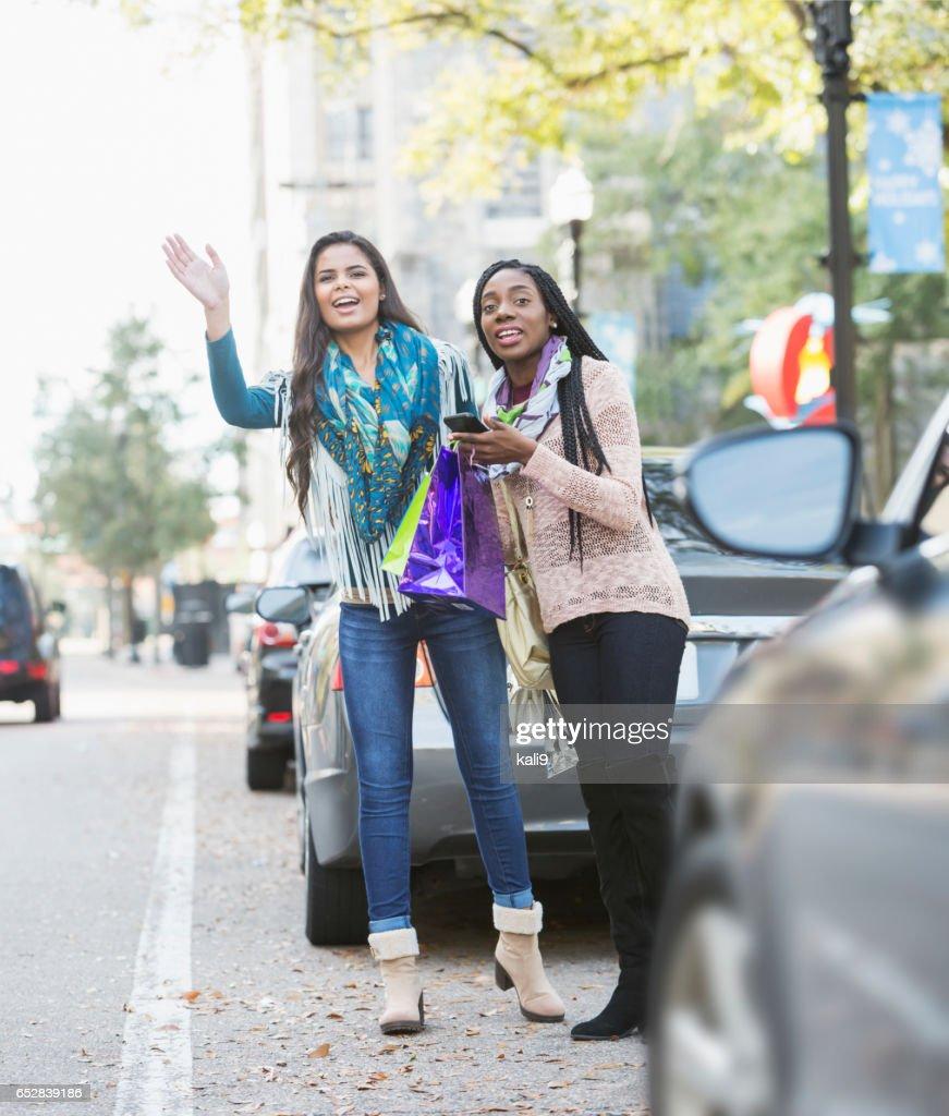 Två multietniska unga kvinnor vinka för taxi : Bildbanksbilder