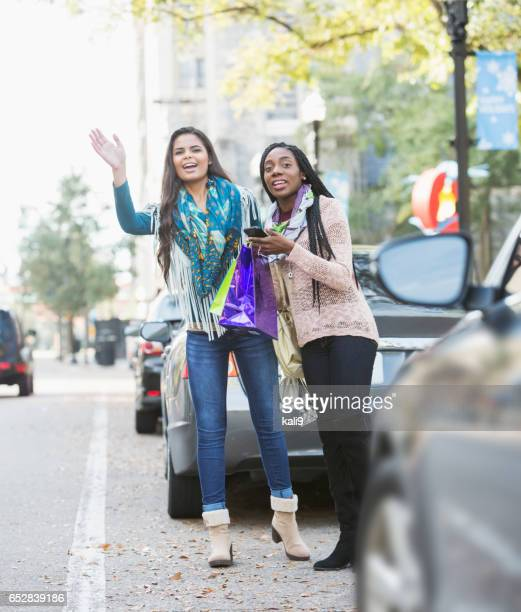 Two multi-ethnic young women waving for taxi