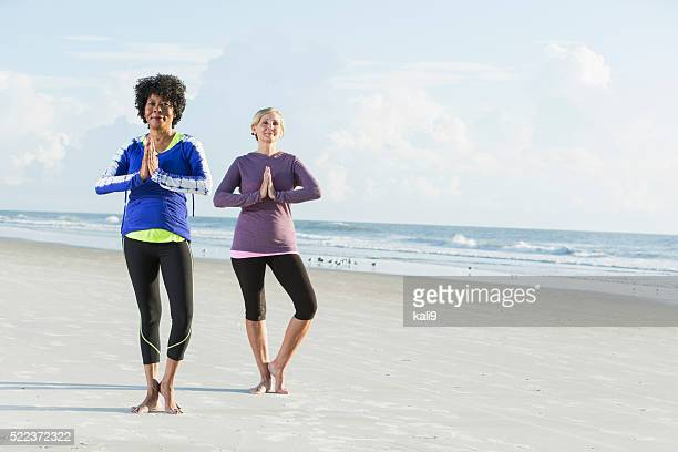two multi-racial mature women doing yoga on beach - tree position stock photos and pictures