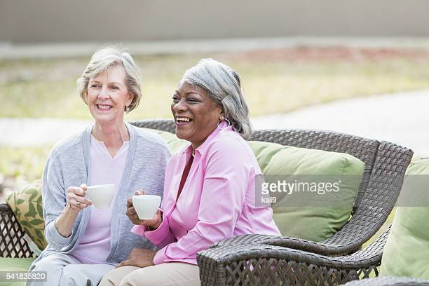 Two multiracial senior women having tea outdoors
