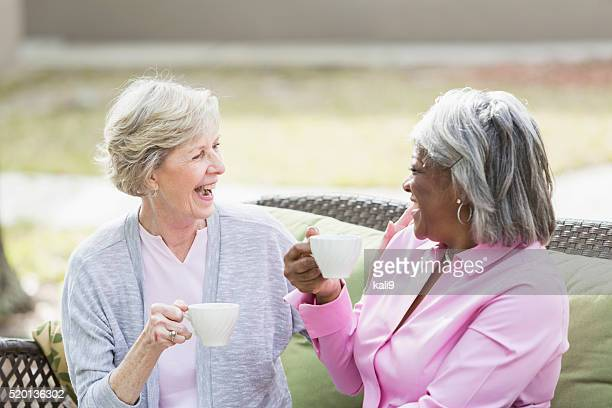 Two multiracial senior women having tea outdoors talking