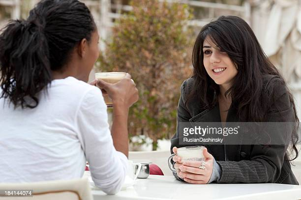 Two multiracial young girls in open-air cafe.