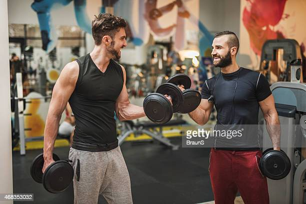 Two muscular build men having weight training in a gym.