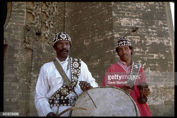 Two musicans one with a large drum stand outside a fortress in Rabat Morocco