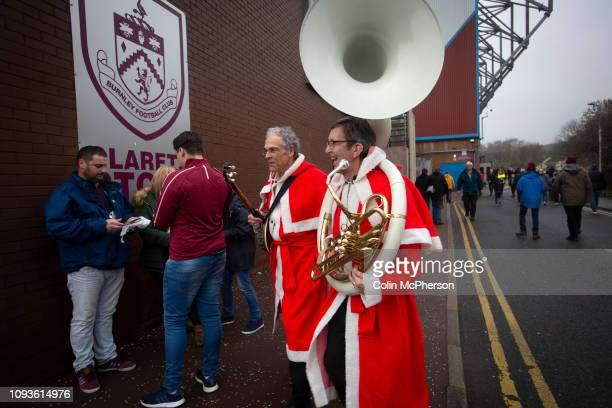Two musicians in Santa outfits making their way towards the stadium before Burnley hosted Everton in an English Premier League fixture at Turf Moor....