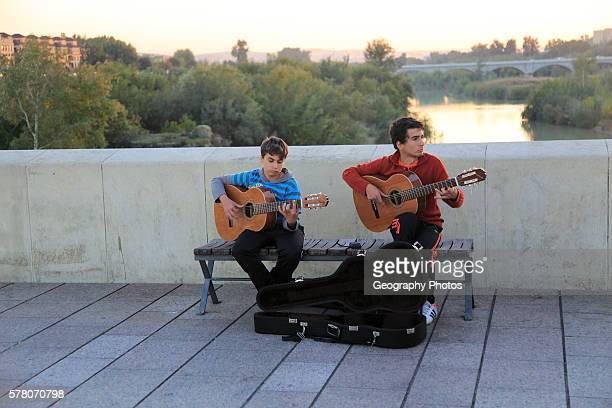 Two musicians playing guitar busking on Roman bridge Cordoba Spain
