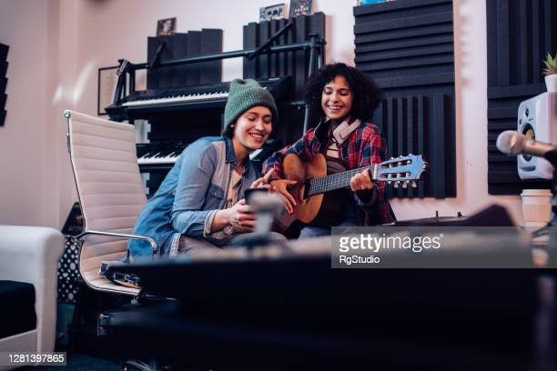 two musicians using smartphone while recording music in the studio - singer songwriter stock pictures, royalty-free photos & images