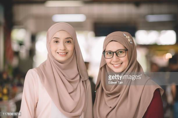 two muslim female malay ladies friend met up at wet market in the morning and greeting to each other - malaysian culture stock pictures, royalty-free photos & images