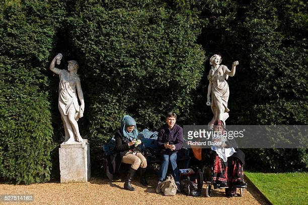 Two Muslim ladies and a European woman sit in sunshine at the National Trust's Hughenden Manor property gardens once home to Benjamin Disraeli This...