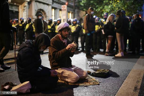 Two Muslim men kneel and pray during a Black Lives matter march through central London on June 6 2020 in London United Kingdom The death of an...