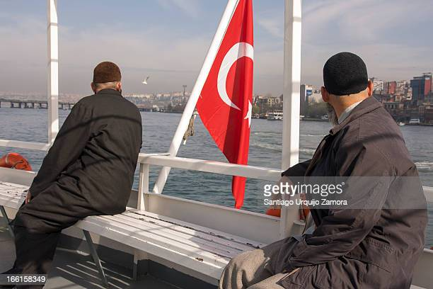 CONTENT] Two Muslim men sitting and looking back on the ferry across the Bosphorus strait with the Turkish flag between them Istanbul Marmara Turkey