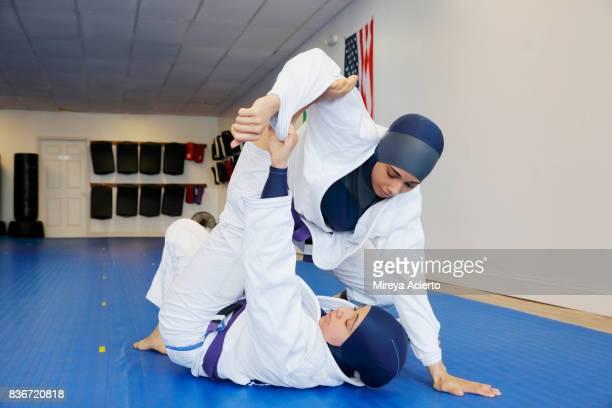 two muslim sisters sparring in jiu jitsu, wearing hijabs. - wrestling stock pictures, royalty-free photos & images