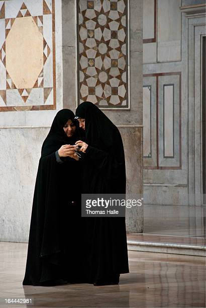 Two Muslim women dressed in all black hijabs looking at their digital camera shortly after posing on the main court at Umayyad Mosque . Damascus,...