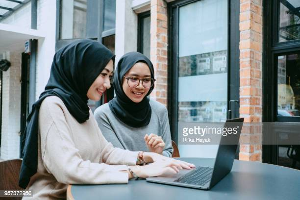 two muslim women is looking at laptop - rifka hayati stock pictures, royalty-free photos & images