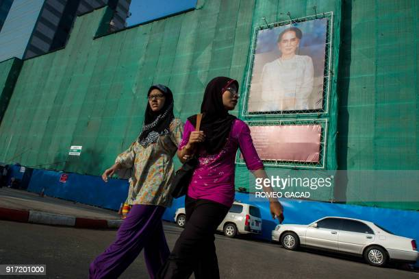 Two Muslim women pass a huge portrait of Myanmar's de facto leader Aung San Suu Kyi displayed on a building construction site overlooking...