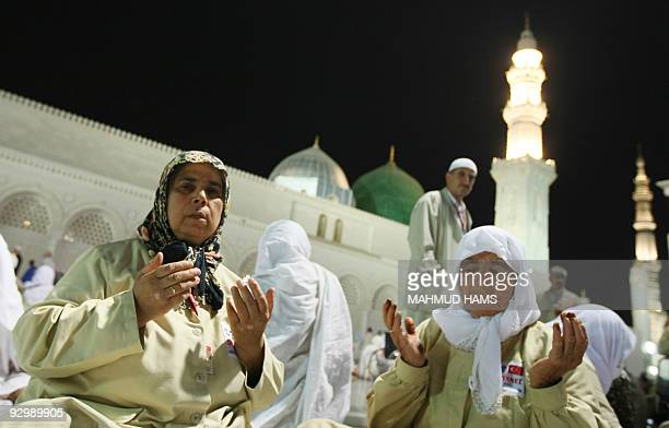 Two Muslim women pray in the courtyard of the Prophet Mohammed Mosque in the Saudi holy city of Medina on November 11 2009 The annual hajj which this...