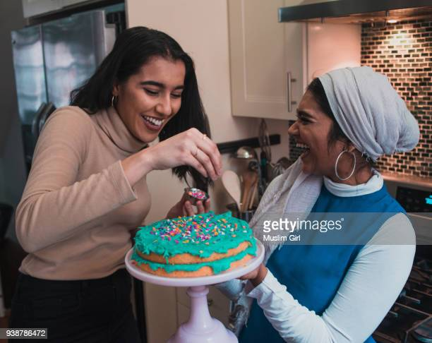 Two Muslim Women Putting Sprinkles Onto a Cake