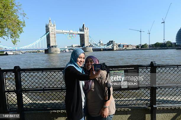Two Muslim women take selfportraits pictures by the Thames river near Tower Bridge bearing the Olympic rings on July 24 2012 in London three days...