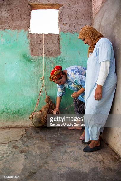CONTENT] Two Muslim women take water from a skinful of goat leather hanging from a window at a house in the village of Bouarfa Figuig Province Morocco