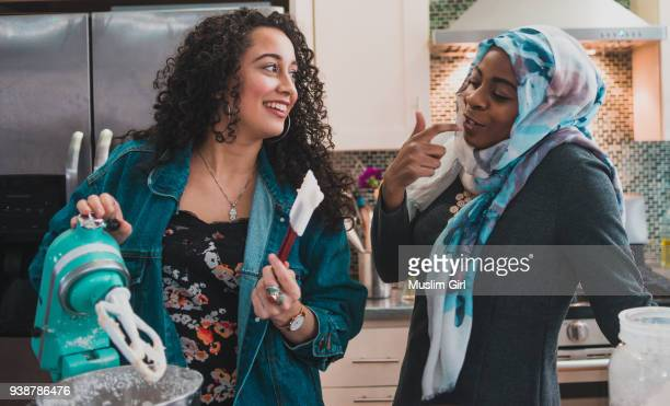 two muslim women tasting cake frosting - muslimgirlcollection stock pictures, royalty-free photos & images