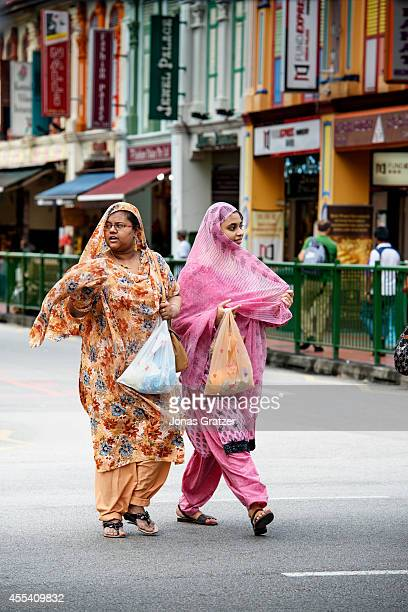 Two Muslim women walk on the road through a shopping and leisure district of the city