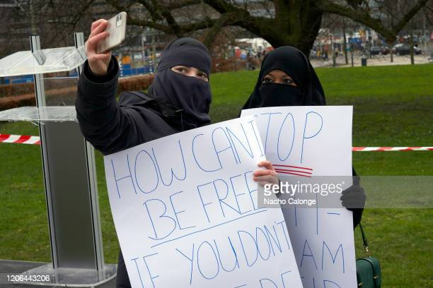 Two Muslim women wearing the niqab take a selfie during the demonstration against the law established by the government banning the use of the niqab...
