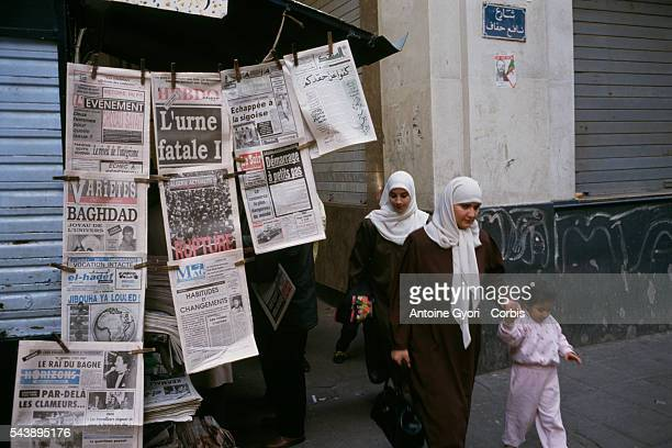 Two Muslim women wearing traditional dress and hijabs and a little girl walk past a newspaper kiosk in Algiers The newspaper headlines refer to the...