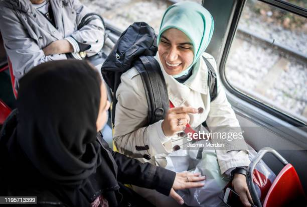 two muslim young woman talking in public transportation - refugee stock pictures, royalty-free photos & images