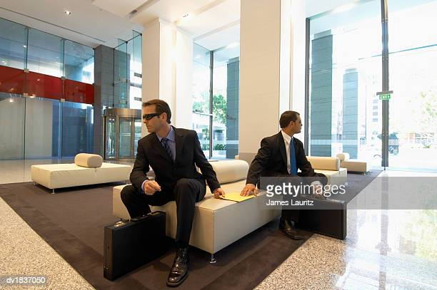 Two Mysterious Men Wearing Suits and Sunglasses Sitting on a Sofa in a Lobby and Passing an Envelope Between each Other