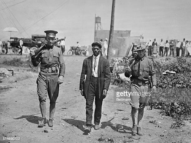 Two National Guard soldiers escort a black man around the time of a race riot in east St Louis