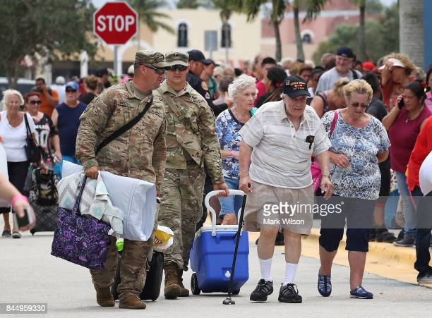 Two National Guardsmen carry the belongings of WWII veteran Anthony Gentuso as he and his famly arrive at the Germain Arena that is serving as a...