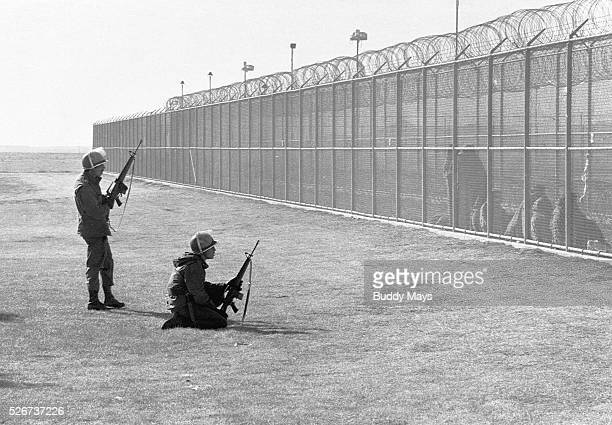 Two National Guardsmen watch prisoners behind a fence after a riot in the New Mexico State Prison
