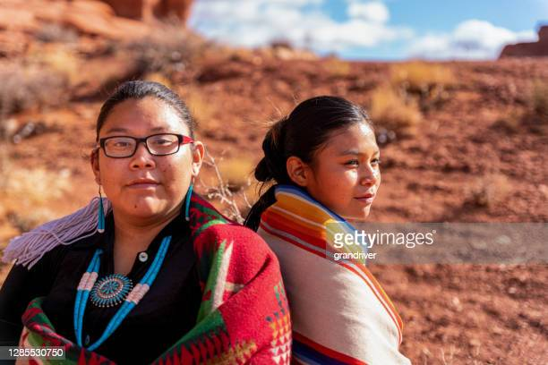 two native american, navajo sisters dressed in traditional clothing, wrapped in a navajo blanket sitting back to back, one looking forward, the other looking away - apache stock pictures, royalty-free photos & images