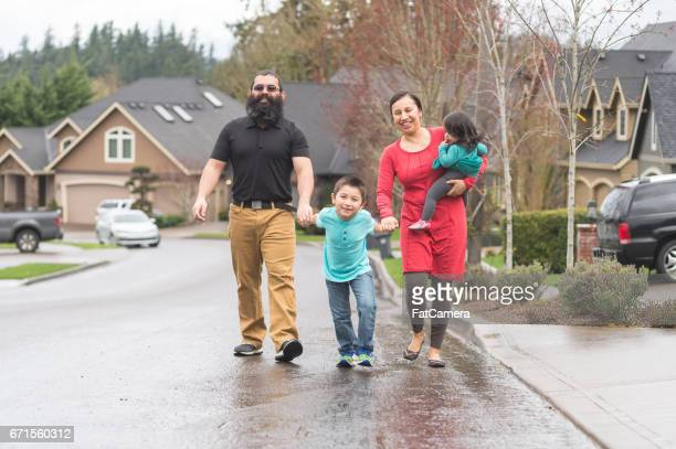 Two Native American parents and their children take a family walk through their suburban neighborhood