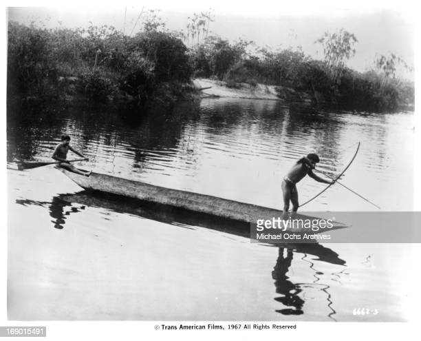 Two natives in a canoe one paddling and the other with a bow and arrow pointed into the water in a scene from the documentary film 'Macabro' 1967