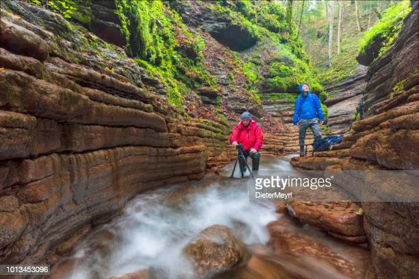 two nature photographer at alpine stream - taugl canyon - tripod stock pictures, royalty-free photos & images