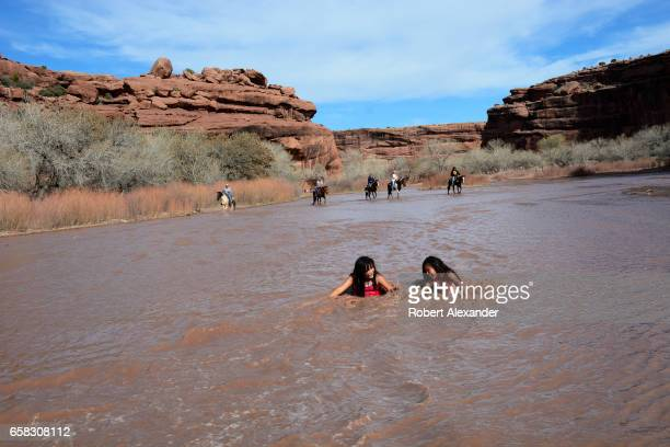 Two Navajo girls play in the muddy water running in Chinle Wash at Canyon de Chelly National Monument near Chinle Arizona as a group of riders on...