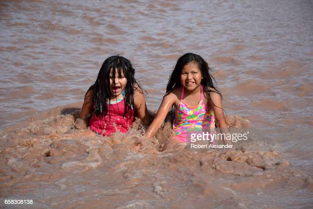 Two Navajo girls play in the muddy water running in Chinle Wash at Canyon de Chelly National Monument near Chinle Arizona Members of the Navajo...