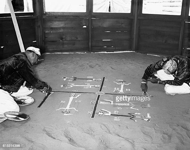 Two Navajo men paint designs on a sand floor for the Navajo Tribal Fair Sand Painting September 1113 1953