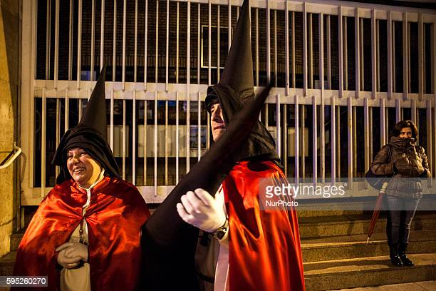 Two Nazarenes of the brotherhood of the passion are glad to have finished the night prayer procession during Holy Week in the city of Santander...