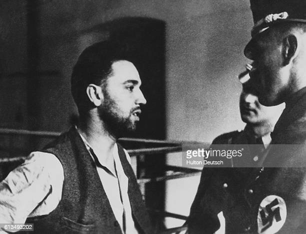 Two Nazi soldiers at Dachau concentration camp interrogate an Austrian prisoner named Spruz a detective who acted as bodyguard to former Austrian...