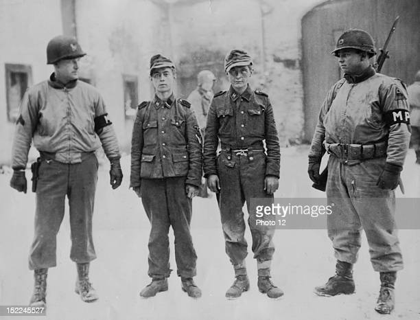 Two Nazi soldiers , captured by troops of the 3rd US, Army on the outskirts of Magerotte , just east of Bastogne .