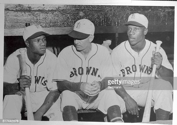 Two Negro players who signed with the StLouis Browns of the American League sit in the dugout with the manager 'Muddy' Ruel prior to the July 17th...