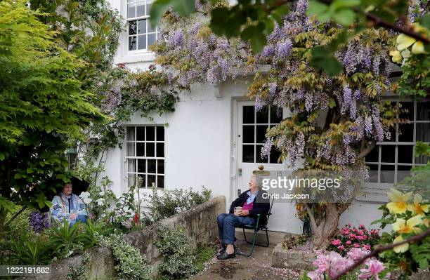 Two neighbours enjoy a socially distanced chat under the wisteria of their houses in Richmond on May 01, 2020 in London, England. British Prime...